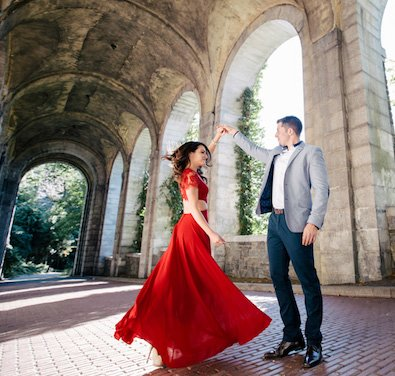 a couple taking enagagement photos in a bright red dress