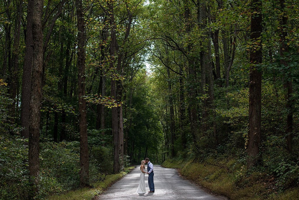 bride and groom photo kissing in middle of road