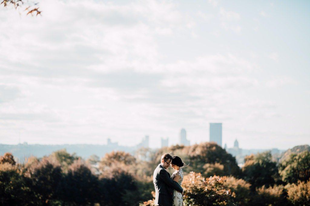 a bride and groom at their wedding with pittsburgh pa in the background