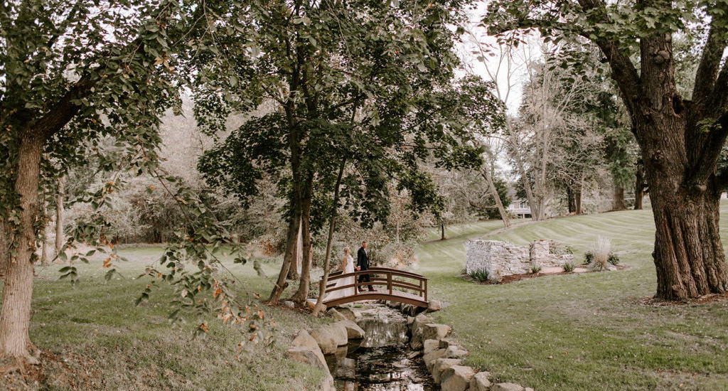 A bride and groom walking over a creek at Historic Ashland, one of the many wedding venues near Lancaster, PA