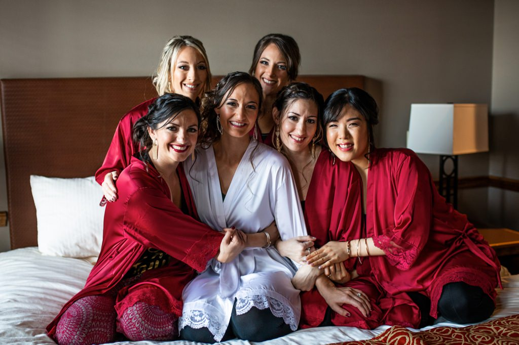 a bride and her bridesmaids posing on a bed while wearing red robes