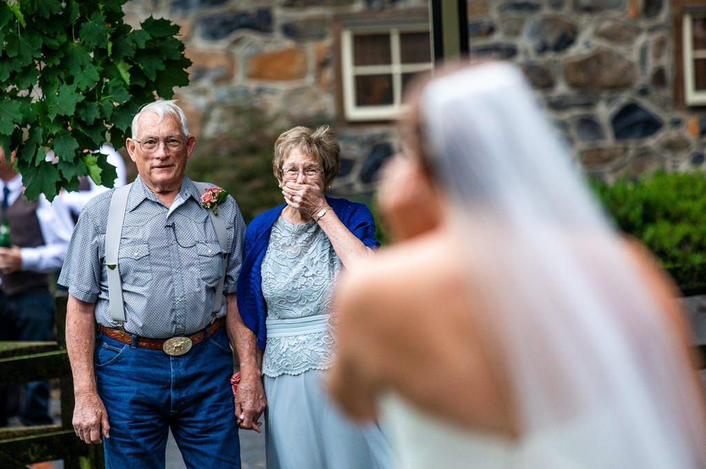A bride doing a first look with her grandparents at a wedding.