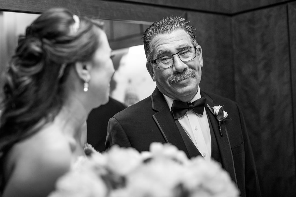 a loving father looking at his daughter on her wedding day.