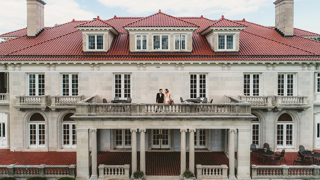 A bride and groom on the balcony of Historic King Mansion, one of the newest wedding venues in Harrisburg, PA