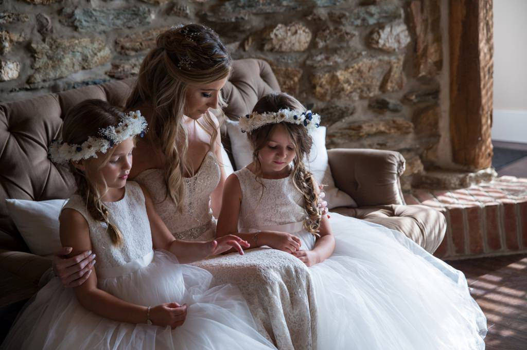 A bride sharing a quite moment with the flower girls before her Wyndridge Farm wedding