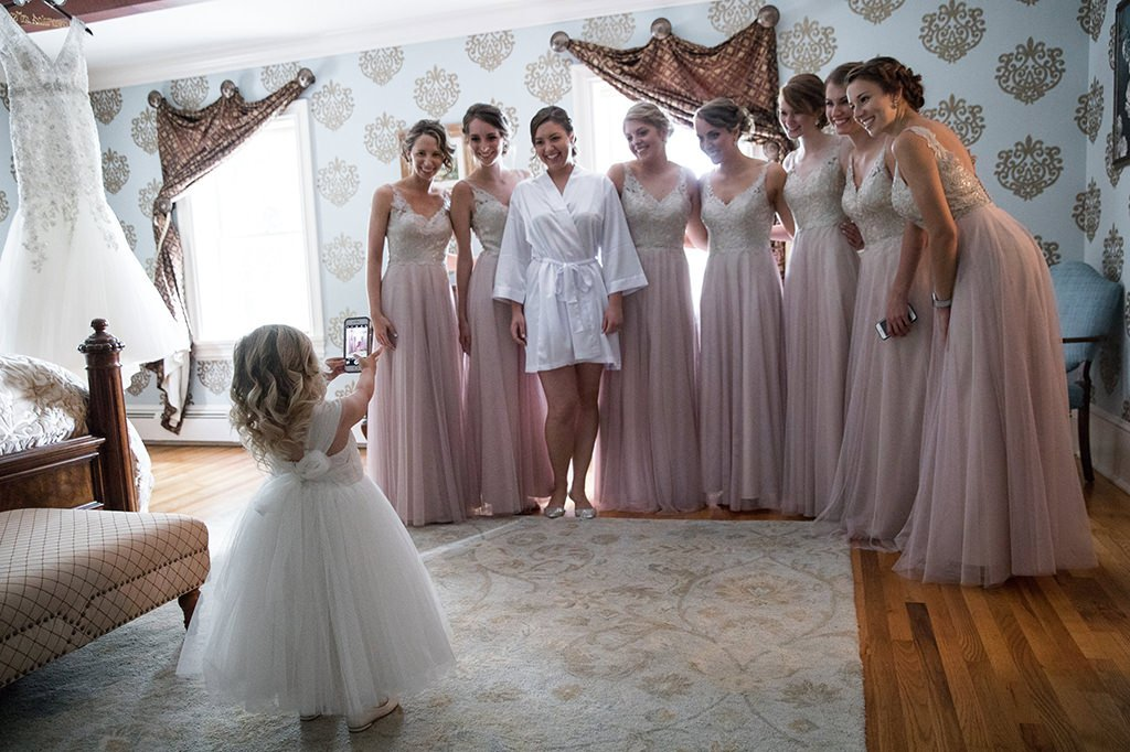 A bride posing with her bridesmaids after looking over the wedding day emergency kit