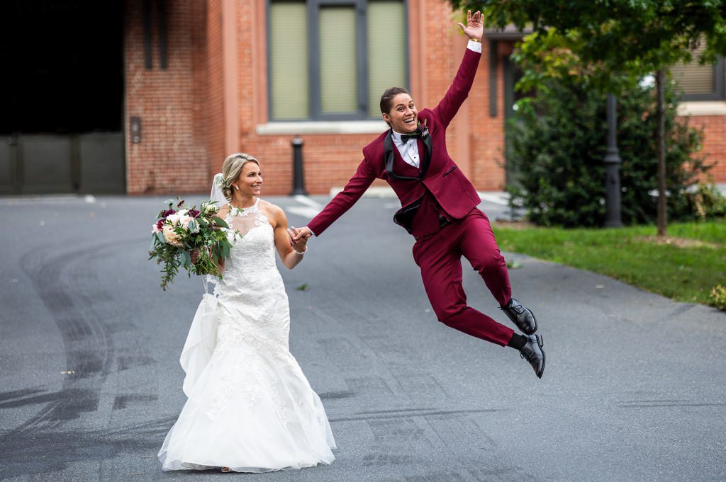 A bride jumping up and clicking her heels after getting married at the Cork Factory Hotel