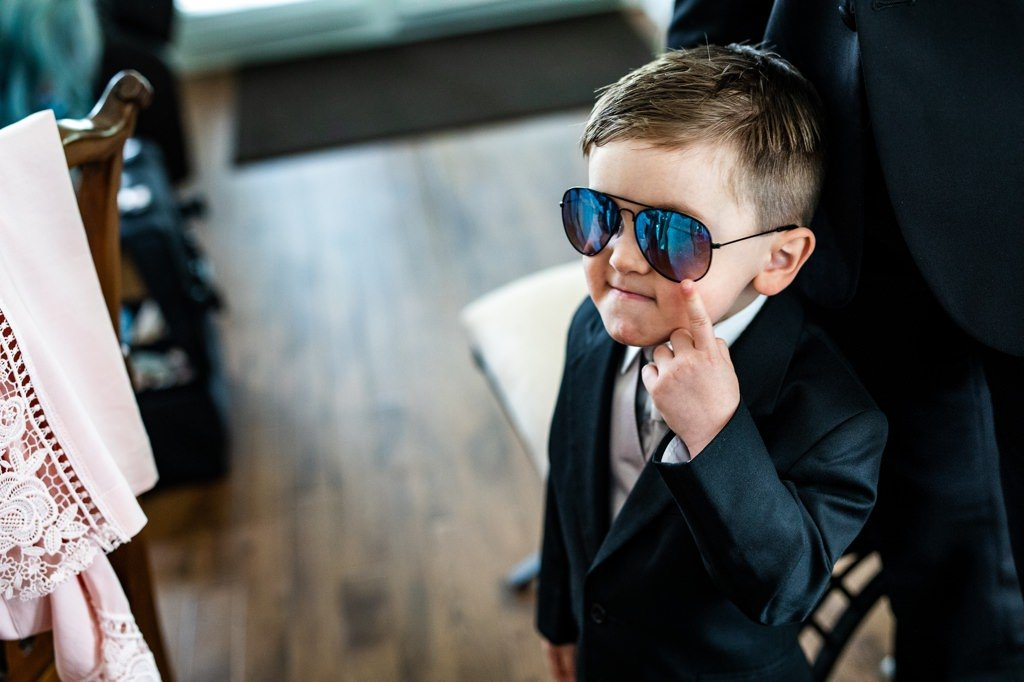 A ring bearer making a funny face while wearing glasses.