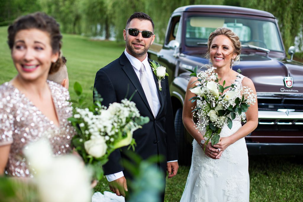 A bride and groom standing next to an old vintage truck