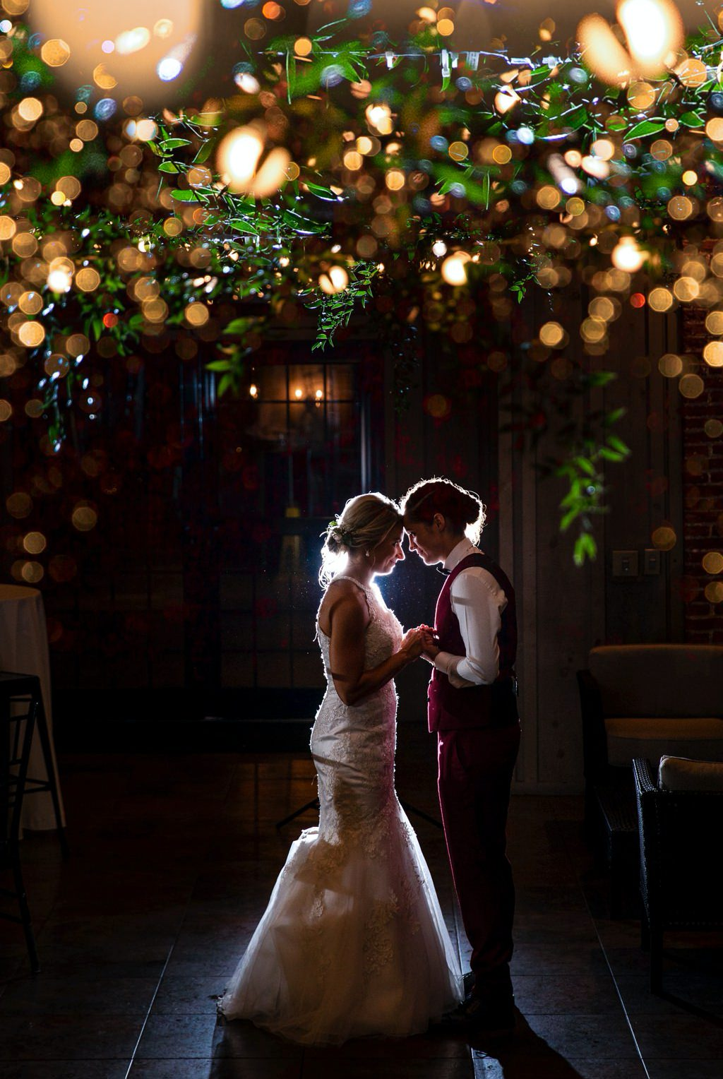 Two brides holding each other under twinkle lights at their Cork Factory Hotel wedding.