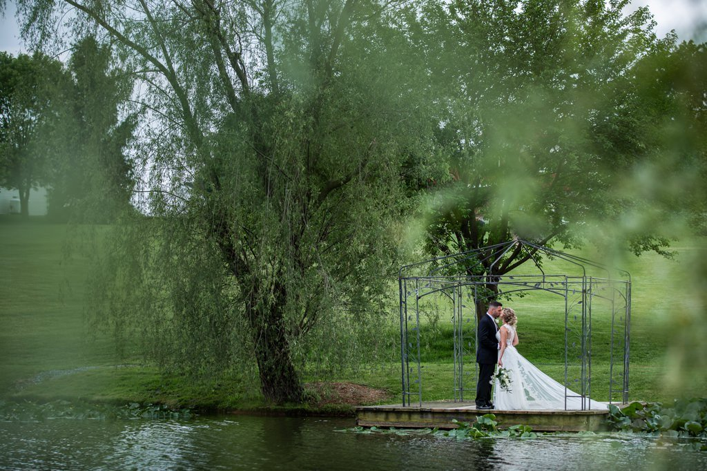 A bride and groom kissing on the dock at Wind in the Willows in Grantville, PA