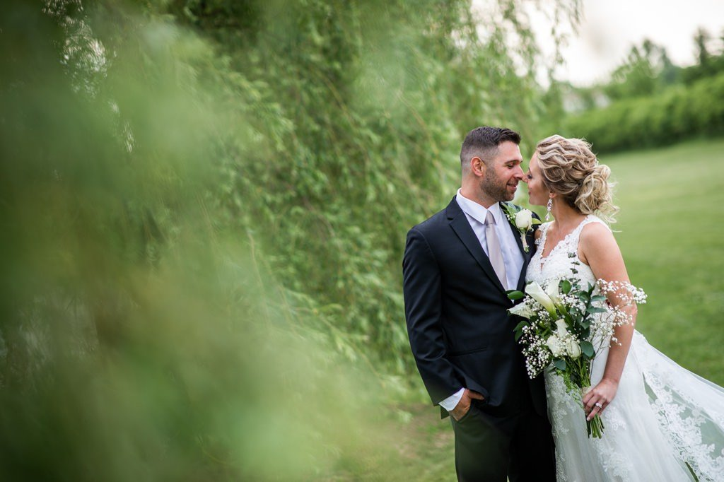 Bride and groom kissing in the willow trees at a harrisburg pa wedding venue