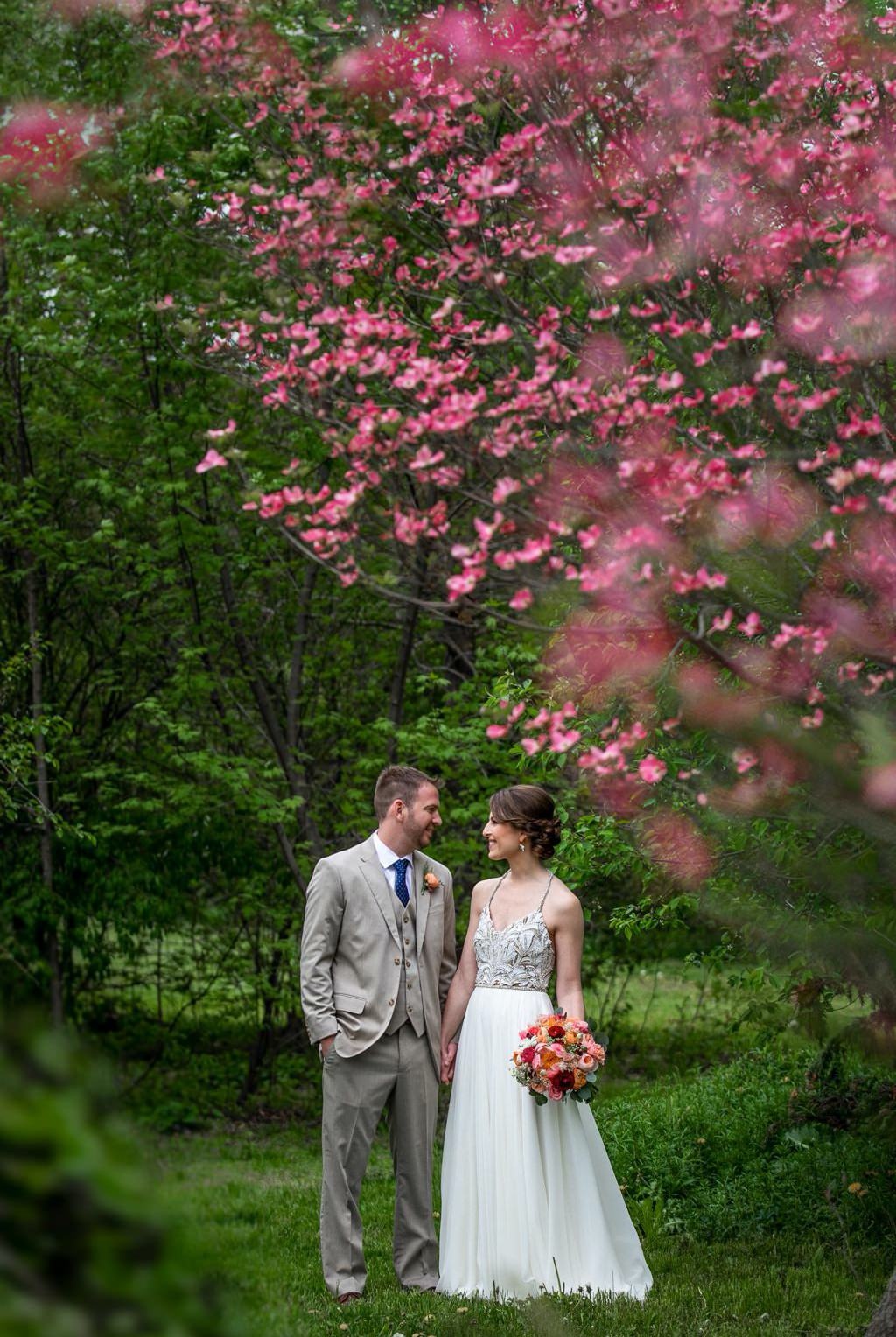 A bride and groom posing in front of a tree with pink blossoms on their wedding day, at The Barn at Silverstone in Lancaster, PA