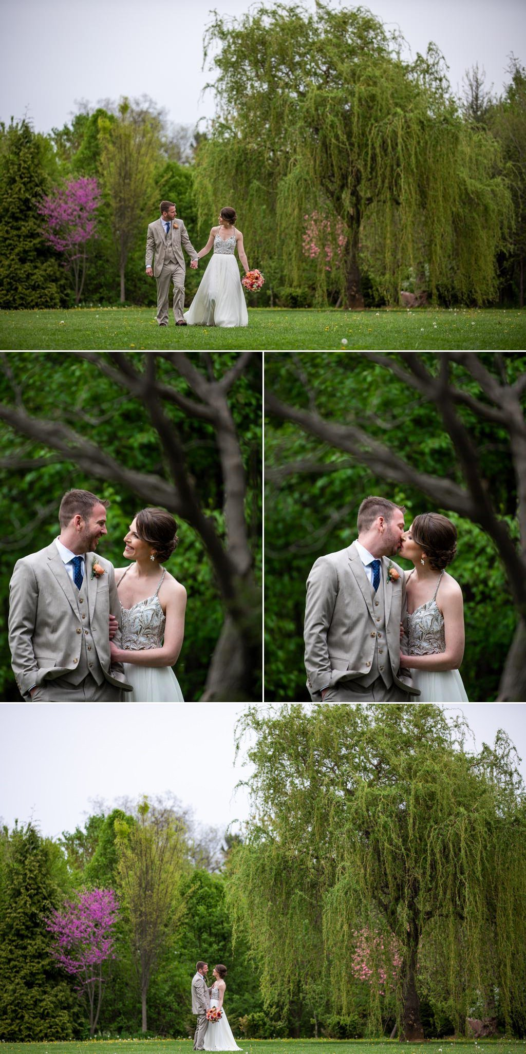 A bride and groom posing for photos near a willow tree at The Barn at Silverstone