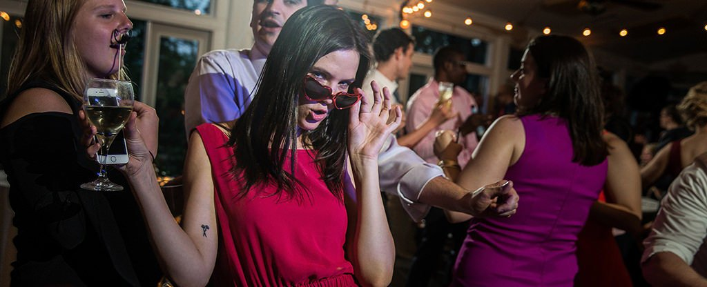 A girl wearing sunglasses as she dances on the dance floor at a fun wedding