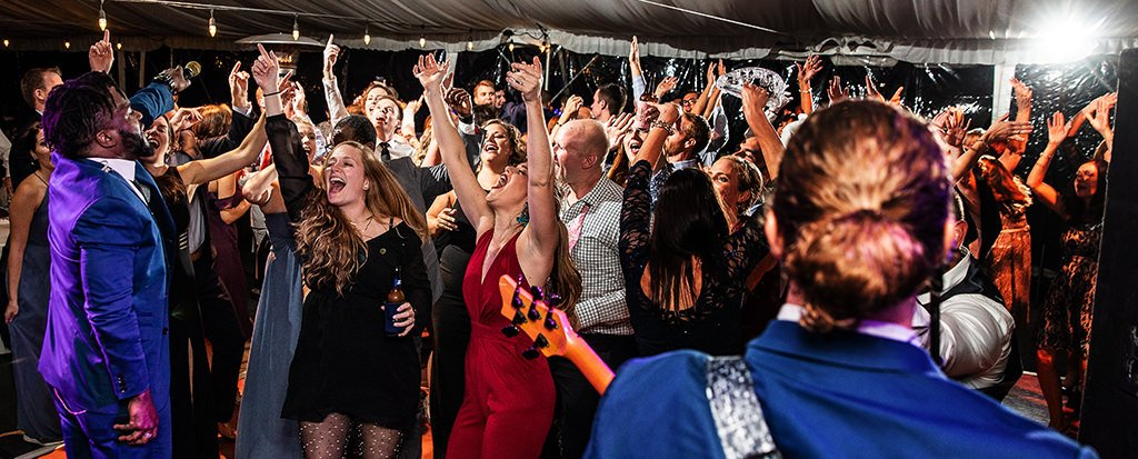 A live band performing the best wedding reception dance songs as the crowd dances and gets crazy