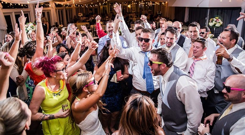 wedding guests dancing to the best wedding reception dance songs on the dance floor.
