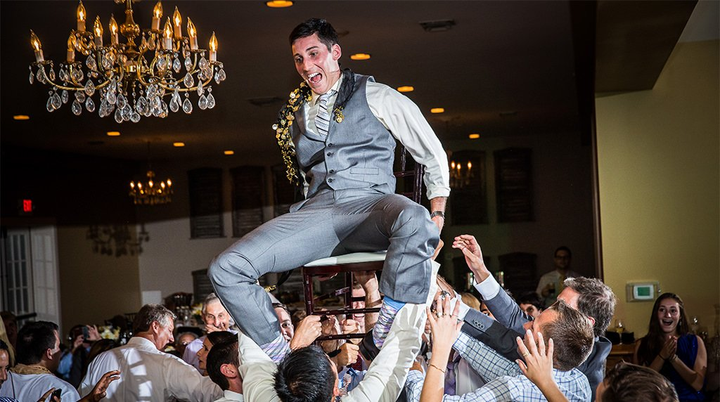 A groom being lifted above the crowd as the guests dance to the best wedding reception songs