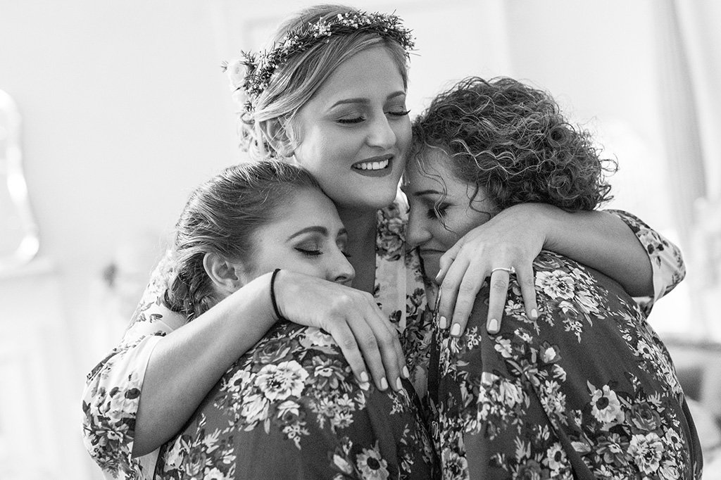 A bride hugging bridesmaids after playing bridal shower games