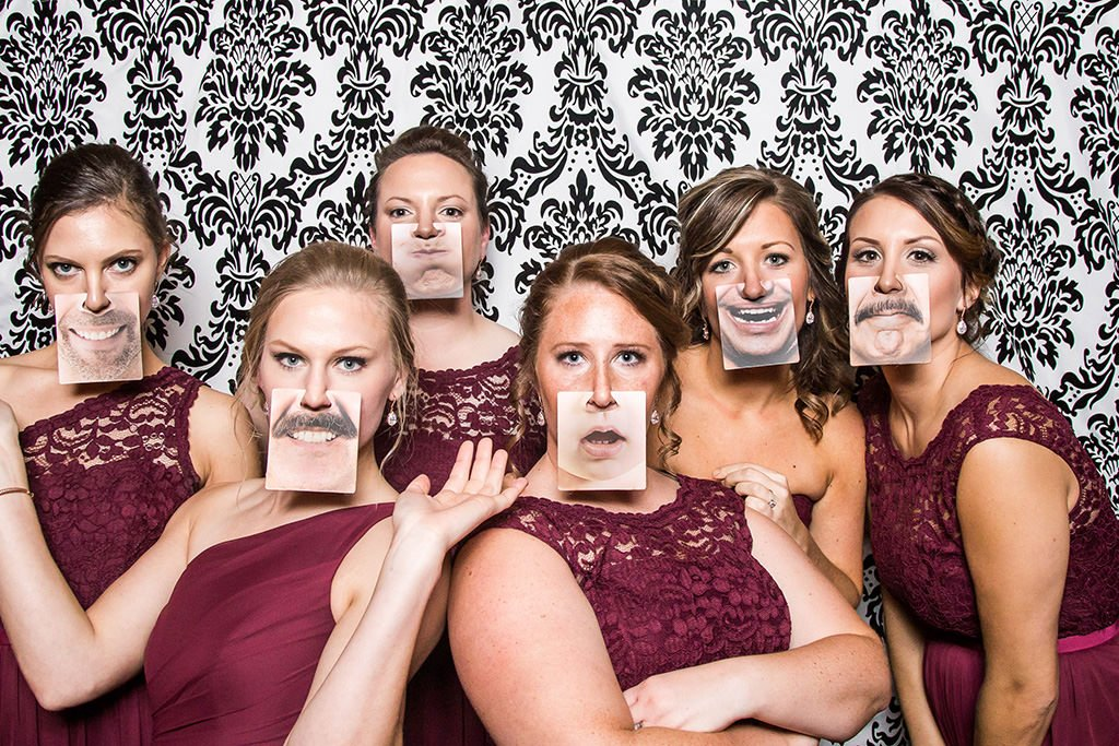 A group of bridesmaids playing bridal shower games with funny face cards