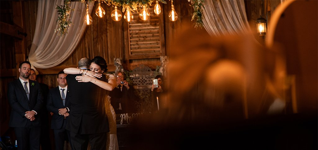 A bride hugging her dad after doing the father daughter dance at the wedding reception. They danced to two of their favorite songs.