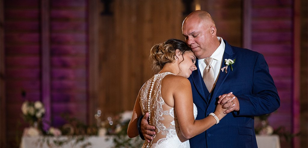 An emotional bride and father of the bride doing a dance together at the wedding reception. They are dancing to their favorite song.