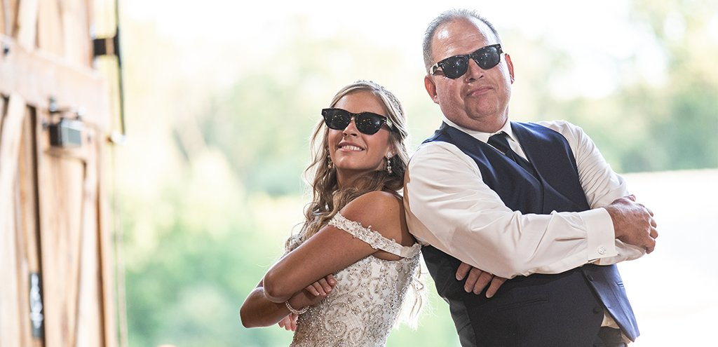 A bride and father of the bride doing a fun wedding reception dance to their favorite songs. Both of them are wearing sunglasses.
