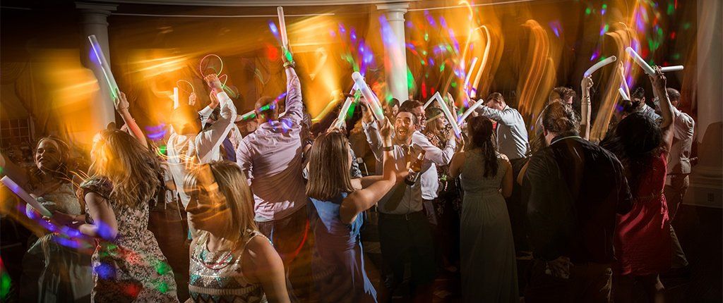 A photo of wedding guests waving glow sticks on the dance floor at a wedding reception. One question to ask your dj is if they can provide something like this.
