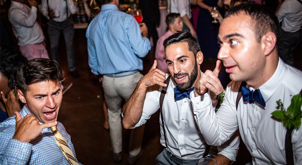 """A photo of 3 guys pretending to talk on the phone. They were dancing to the song """"call me maybe"""" at a wedding reception."""