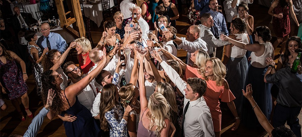 A big group of people doing cheers with drinks on a wedding reception dance floor.