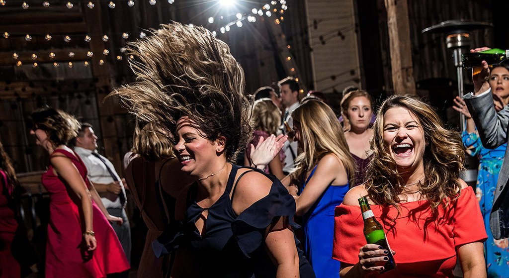A girl flipping her hair over her head as she dances to the best wedding reception dance songs