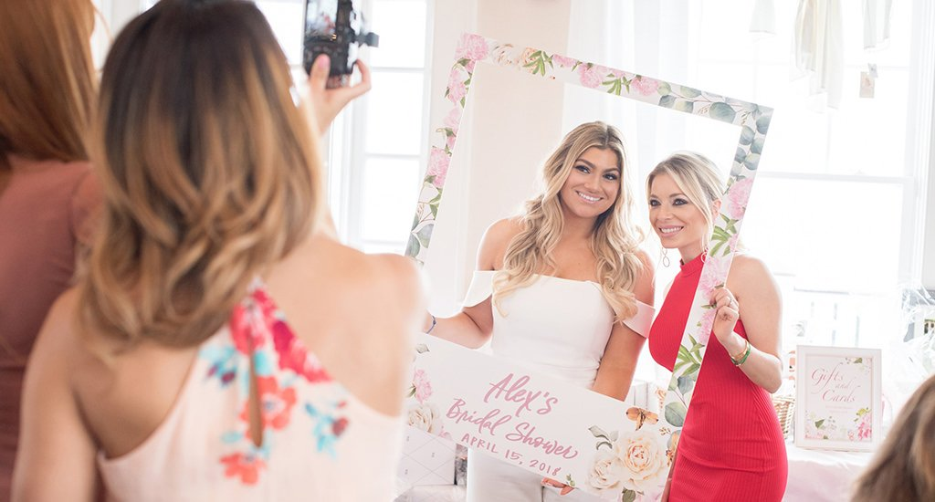 A bride and friend posing for photos at a bridal shower. Made for the what is a bridal shower post.