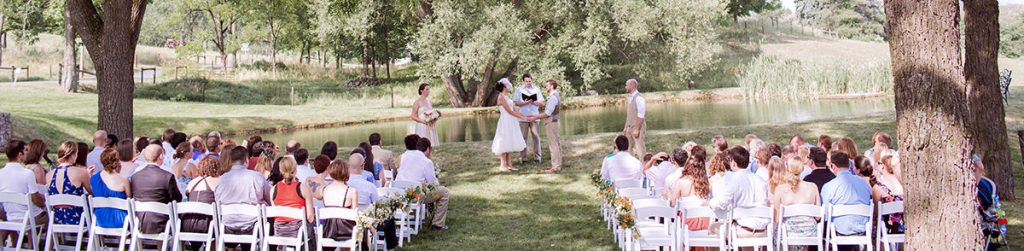 a backyard wedding ceremony taking place near a pond