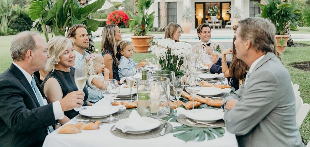 a fmaily having dinner at a backyard wedding