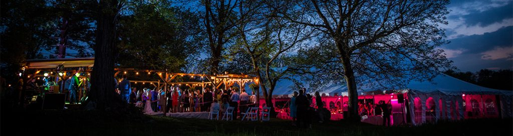 a backyard wedding reception taking place at night. This is a photo of the tent and dance floor lit up by lights