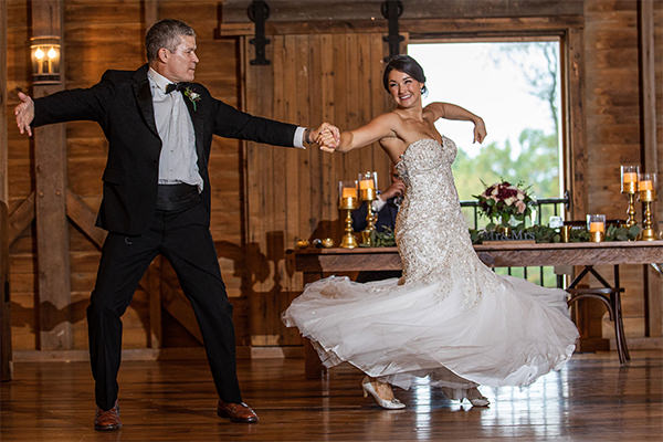 A father and daugher dancing to the best wedding songs at a wedding ceremony and reception