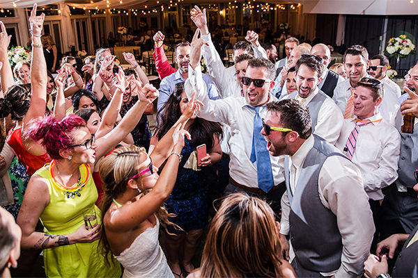 A fu group of people dancing at a wedding reception. Everyone has their hands in the air.