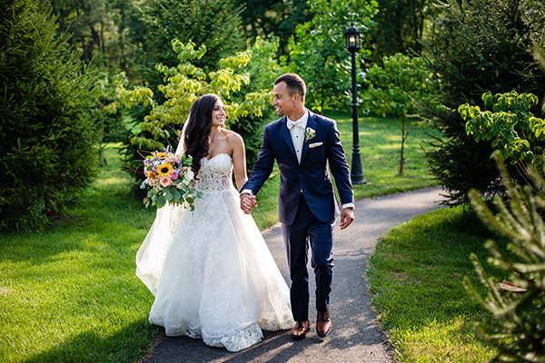A bride and groom walking down a path looking at each other. This is for the pittsburgh pa bridal shop section of the page.