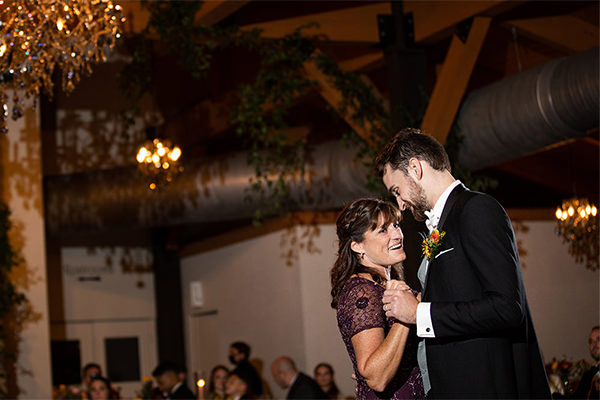 a mother and her son dancing at the wedding reception