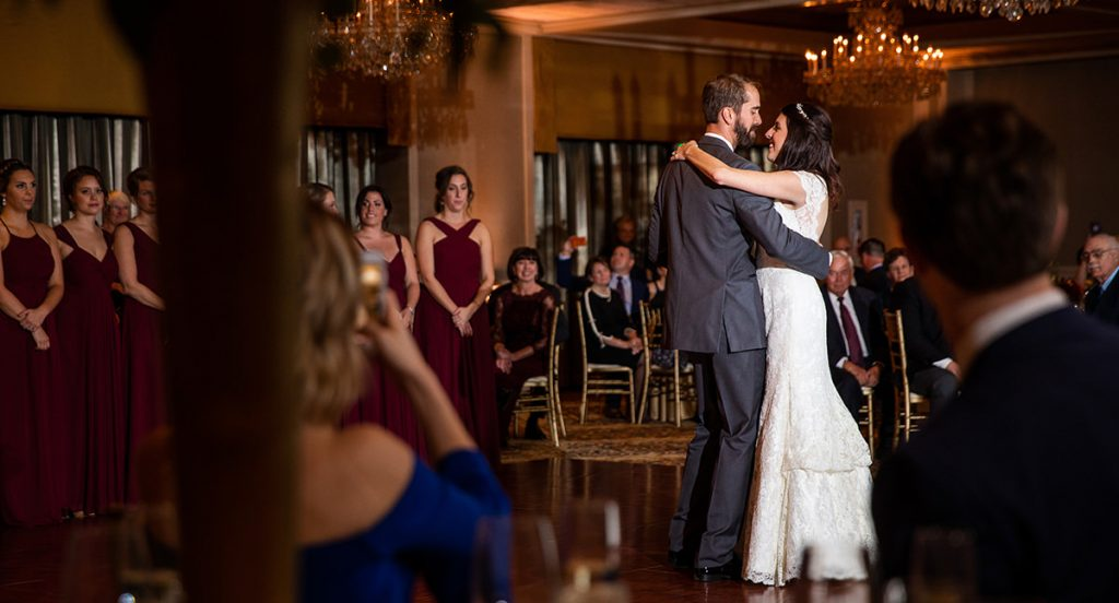 A bride and groom dancing their first dance to a frank sinatra song at their wedding reception. Lots of guests are watching