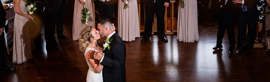 A bride kissing the groom on the dance floor during their wedding first dance.