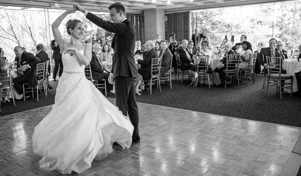 a groom spinning the bride on the dance floor during their first dance. They are dancing to a Dean Martin song