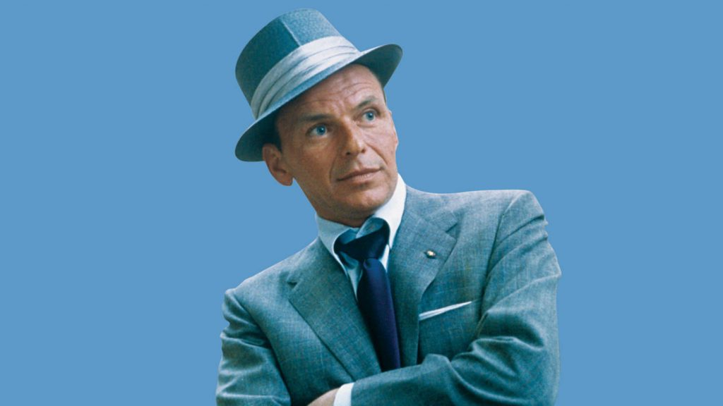 frank sinatra posing in a hat. This is the cover photo for an article called frank sinatra wedding songs.
