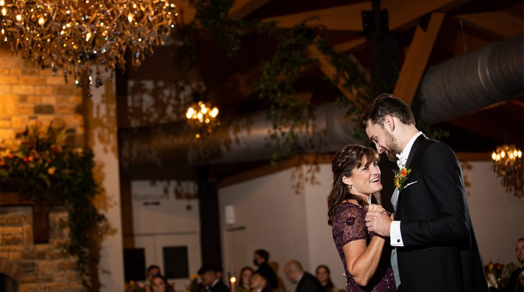A mother dnacing with her son at a wedding reception. they are dancing to Michael buble.