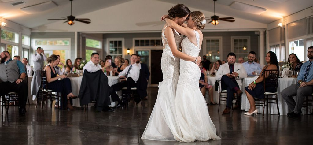 Two brides holding each other during their wedding reception first dance.