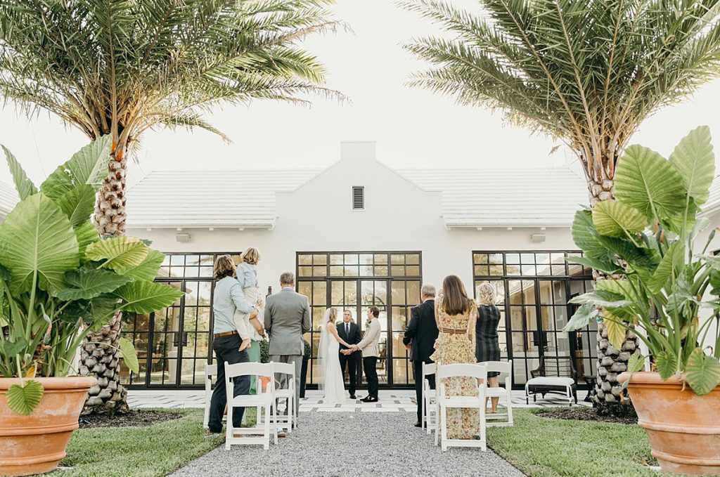 a small intimate micro wedding in a beautiful backyard. This photo shows the bride and groom getting married right in front of a house.