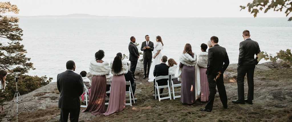 A bride and groom getting married in a micro wedding along the coastline of the atlantic ocean