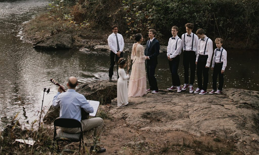 A small intimate micro wedding next to a river. In this photo is a small wedding taking place with a bride, groom, pastor, 5 children, and a man playing an acoustic guitar.