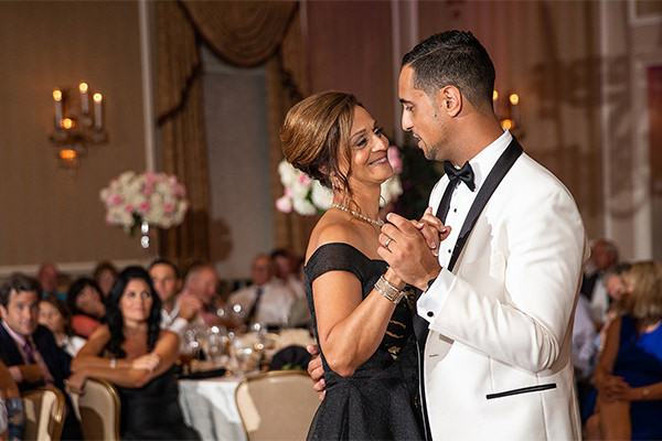 A mother and son sharing a dance at a wedding reception. They are dancing to their favorite song