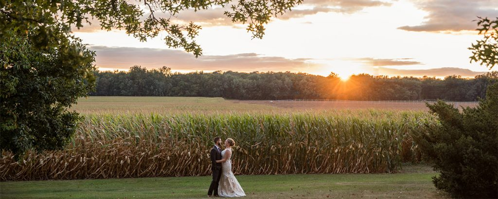 A bride and groom dancing near a cornfield after their small elopement wedding. The sun is setting behind them.
